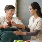 Caregiver serving the elder woman some fruits to eat