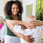 Caregiver assisting the elder man doing his exercise
