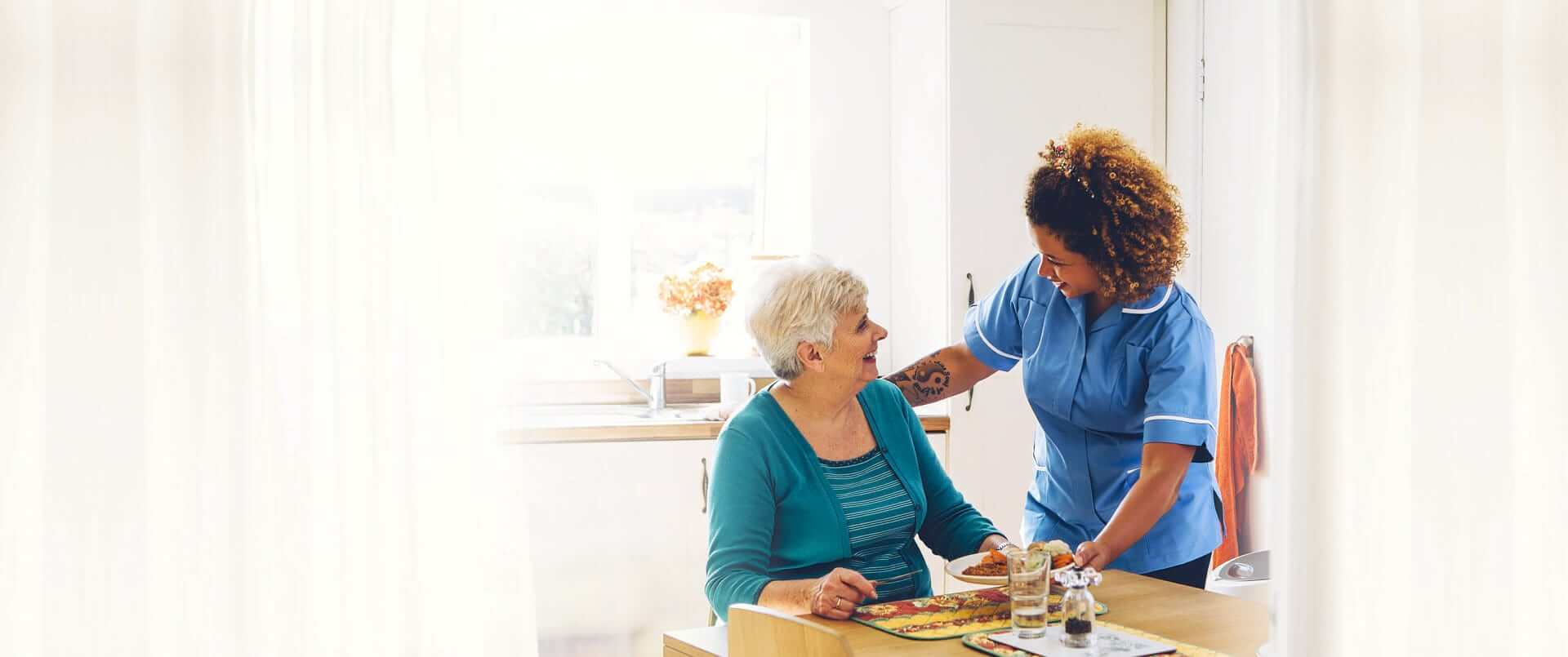Caregiver serving the elder woman her meal