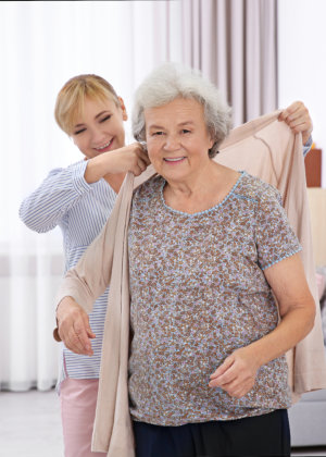 Caregiver helping the senior woman to put on her cardigan