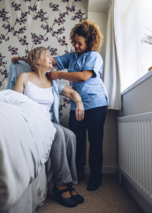 home caregiver helping senior woman